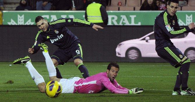El delantero francés de Real Madrid Benzemá (izq.) supera la salida del portero Toño (en el suelo), del Granada, durante el partido de Liga disputado el sábado 2 de febrero en el estadio de Los Cármenes.