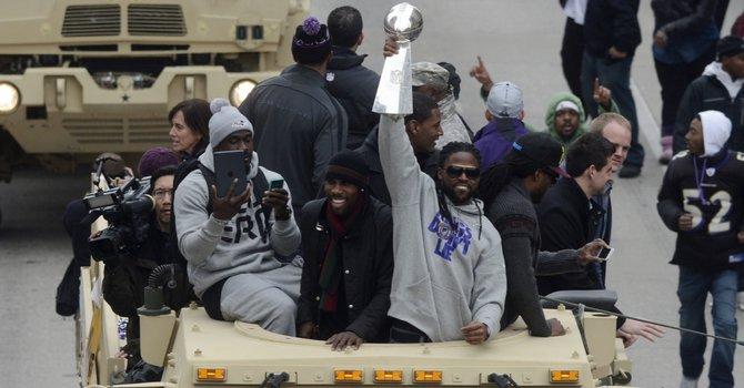 El jugador de los Ravens de Baltimore, Torrey Smith (centro), levanta la copa Vince Lombardi el martes 5, durante el desfile triunfal de los campeones del Super Bowl XLVII en Baltimore, MD.