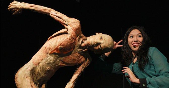 """Una salvadoreña posa con un cuerpo de la reconocida exposición China """"Our Body: El universo dentro"""" el martes 5 de febrero en San Salvador, El Salvador."""
