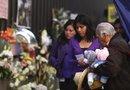 Empleados de Petróleos Mexicanos (PEMEX) colocan flores en el enrejado durante su regreso al edificio de la compañía.