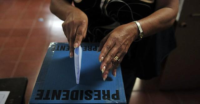 Una mujer deposita su voto en unas elecciones presidenciales en El Salvador