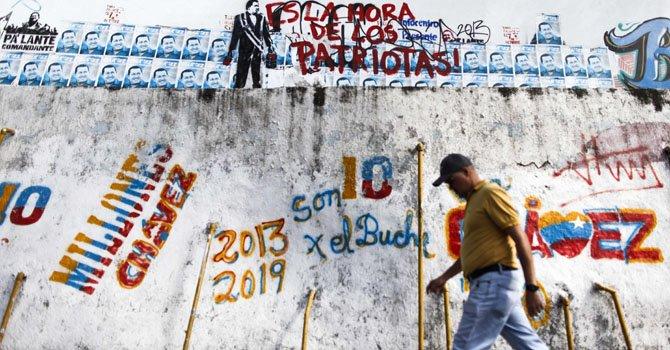 Un hombre camina junto a letreros pintados con mensajes alusivos al presidente de Venezuela, Hugo Chávez, el viernes 8 de febrero.