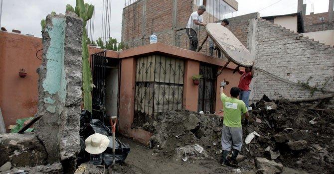 Residentes rescatan sus pertenencias hoy, lunes 11 de febrero, después de que intensas lluvias ocasionaran deslizamientos en Arequipa, Perú.