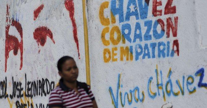 Una mujer camina junto a un letrero pintado con un mensaje alusivo al presidente de Venezuela, Hugo Chávez.