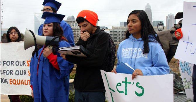 Los Dreamers de Carolina del Norte (de izq. a dcha.) Jessica Contreras, Jorge Acosta, y Estefanía Ventura sostienen pancartas y gritan consignas durante una marcha celebrada en un parque del centro de Charlotte.