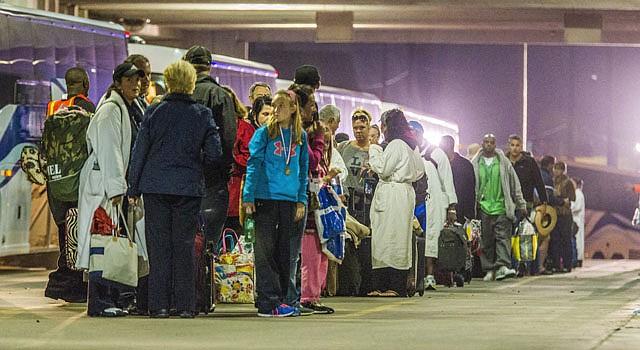 Pasajeros esperan para subir a bordo de un autobús que les recogió al desembarcar del crucero 'Triumph, tras permanecer en el Golfo de México durante cinco días sin propulsión a motor ni climatización, y con escasez de alimentos, retretes y corriente.