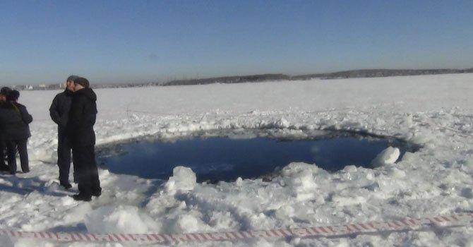 Unos hombres paseando al lado de un agujero de ocho metros en el lugar donde un meteorito impactó, en el lago congelado Chebarkul, cerca de Cheliabinsk, Rusia el viernes 15 de febrero.