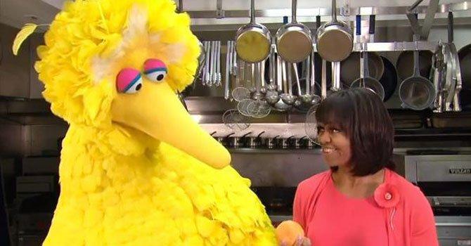 La primera dama Michelle Obama (der.) con un personaje del programa Sesame Street's Big Bird en la cocina de la Casa Blanca en Washington. La primera dama y Big Bird protagonizan un par de anuncios de interés público que serán distribuidos a más de 300 estaciones de radiodifusión pública a lo largo del país.
