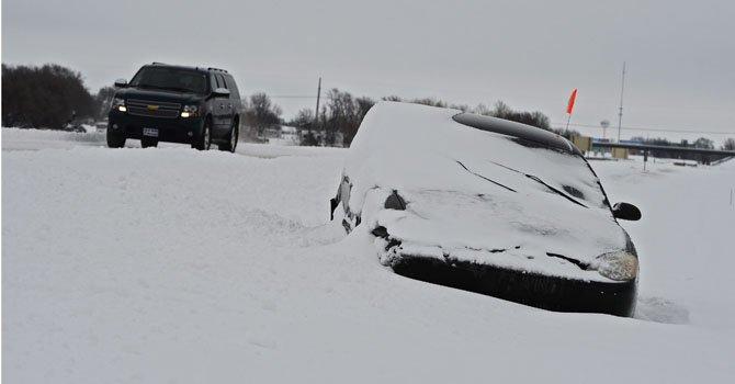 Un automóvil permanece sepultado por la nieve en una carretera situada en Wichita, Kansas, el jueves 21 de febrero. Un frente de nieve recorre el centro del país.
