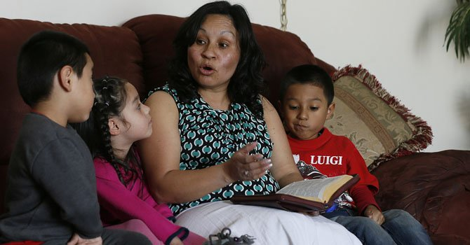 Ana Cañenguez, una madre salvadoreña residente en Utah que ha vivido un verdadero periplo para mantener a sus hijos, les lee la Biblia a sus hijos Katherine, Luis, y a su nieto Easau en su casa de Treemonton, Utah.