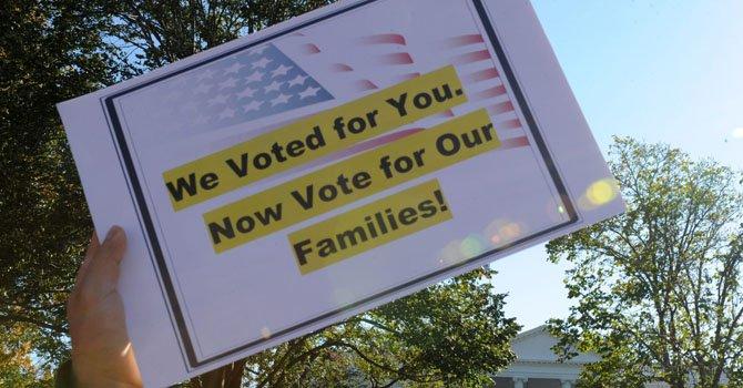 """Una persona muestra un cartel que dice """"Hemos votado por tí, ahora vota por nuestras familias"""" el 8 de noviembre 2012, durante una manifestación ante la Casa Blanca en Washington, DC."""