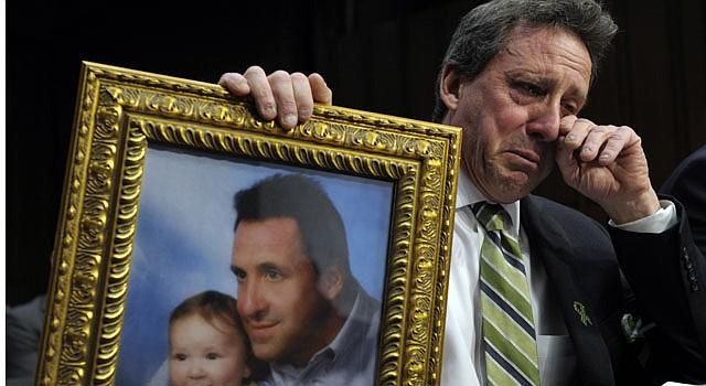 Neil Heslin, padre de un niño de 6 años asesinado en la masacre de la escuela Sandy Hook en Newtown, Connecticut, el 14 de diciembre de 2012, sostiene una fotografía de él con su hijo Jesse mientras contiene las lágrimas al dar su testimonio en el Capitolio en Washington, el miércoles 27 de febrero de 2013, en una audiencia sobre el control de armas.