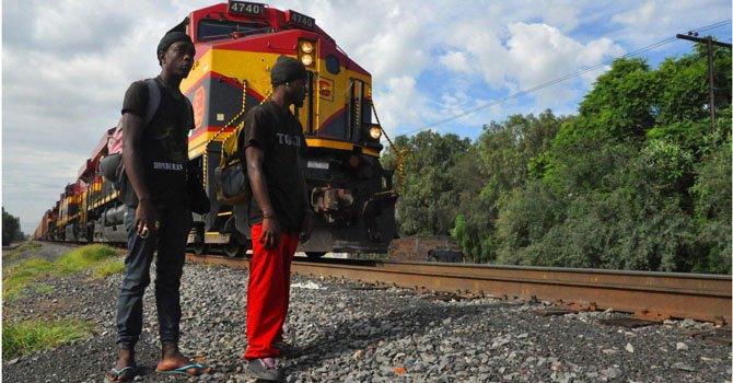 """Dos ciudadanos hondureños se preparan para correr al paso de """"La bestia"""" , el tren mexicano que recorre México rumbo a la frontera de EEUU."""
