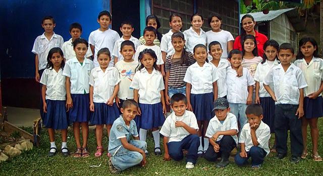La maestra Vanessa García (atrás de rojo) posa con un grupo de alumno, en la población de Buenos Aires de Villafranca (Honduras). García es una de los muchos docentes en el país que se tienen que multiplicar por tres o seis para impartir clases en escuelas de aldeas remotas.