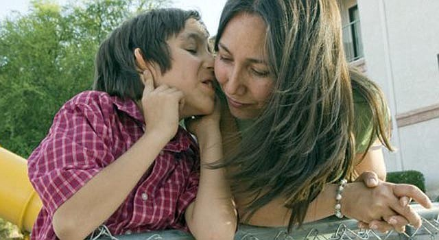 """La mexicana Rosario Messina escuchando a su hijo autista Andre en el patio de un edificio de viviendas de Tucson, Arizona, en el que cada mes se reúnen las madres de la organización """"Ángeles con autismo""""."""