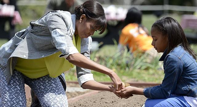 La primera dama estadounidense, Michelle Obama (i) ayuda a Ariana Docanto (d), una estudiante de quinto curso en la escuela de Arthur D. Healey, a plantar semillas durante la quinta edición de cultivo de la Casa Blanca celebrada en el jardín sur de la residencia presidencial en Washington, Estados Unidos el 4 de abril.