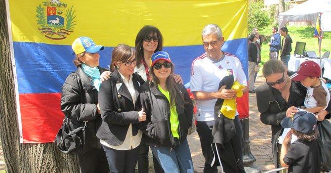 Una familia venezolana comparte al frente de una gran bandera instalada en el comando de la organización de voluntarios Voto en Washington en las cercanías de la embajada de ese país en Georgetown, Washington, DC, el domingo 14 de abril.