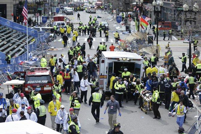 Socorristas asisten a los heridos en la línea de meta del maratón de Boston, cerca de donde ocurrieron dos explosiones, el lunes 15 de abril.