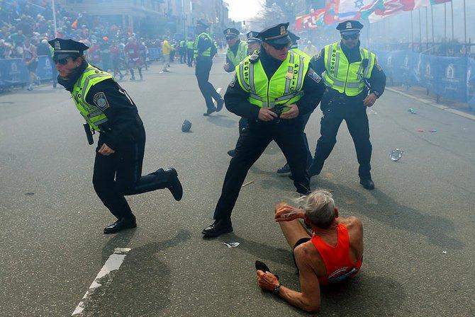 Policías frente a un maratonista que cayó al suelo al estallar una de las bombas.