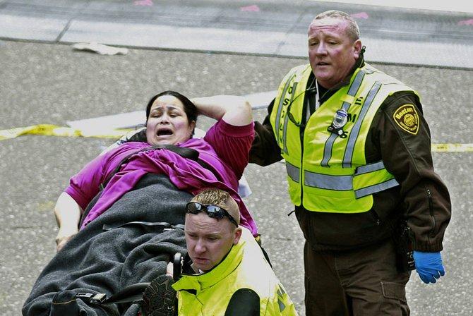 Miles de los espectadores de la maratón entraron en pánico al ver las horribles escenas. Rescatistas asisten a una mujer herida.