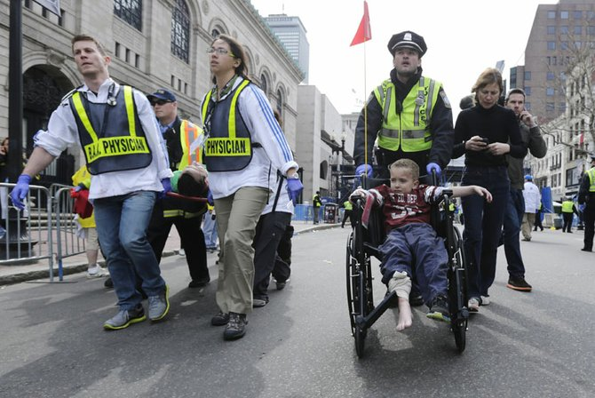 Socorristas ayudan a un niño y a su madre que resultaron con heridas menores tras las explosiones en la Maratón de Boston.