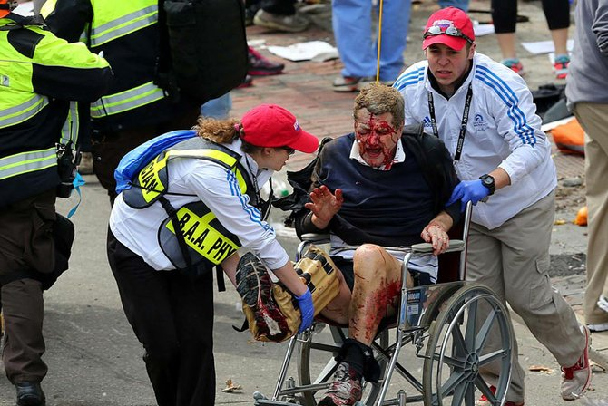Rescatistas ayudan a un hombre que sangraba tras las heridas que sufrió por las explosiones de las bombas en Boston.