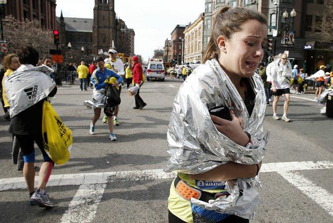 Una maratonista llora al ver la tragedia que dejó a tres muertos y más de 140 heridos en la Maratón de Boston al estallar dos bombas.