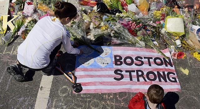 Una mujer y su hijo llevan flores a un altar en Boston el domingo 21 de abril.