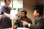 Mariano Claudio (derecha) habla con el abogado Lawrence Tucker del caso del Sr. Callejas (centro) a quien ayudaron a salvar su casa.