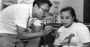 PIONERO. El doctor Juan Romagoza, quien dirigió la clínica por dos décadas desde 1988 hasta 2008, asiste a una paciente en el antiguo local.
