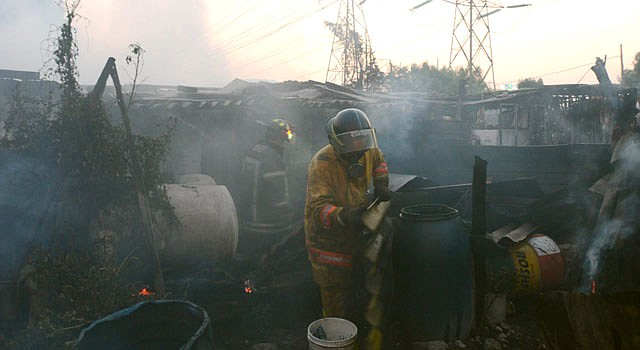 Un bomberos despeja un área tras el incendio en unas viviendas luego de la explosión de un camión cisterna cargado con gas el martes 7 de mayo, y que dejó al menos 18 muertos y 36 heridos en el municipio de Ecatepec, en el centro de México, informaron fuentes oficiales.