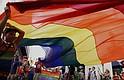 Participantes agitan una bandera símbolo de la comunidad LGBT.