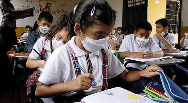 Estudiantes asisten a clases usando tapabocas, como parte de las medidas de protección contra la gripe AH1N1 en el país.