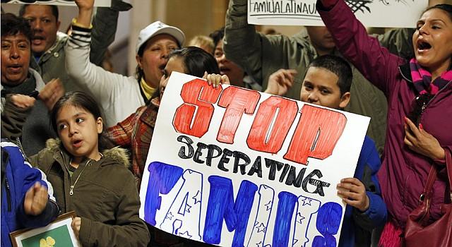 Unos niños sostienen una pancarta que pide un alto a la separación de familias.
