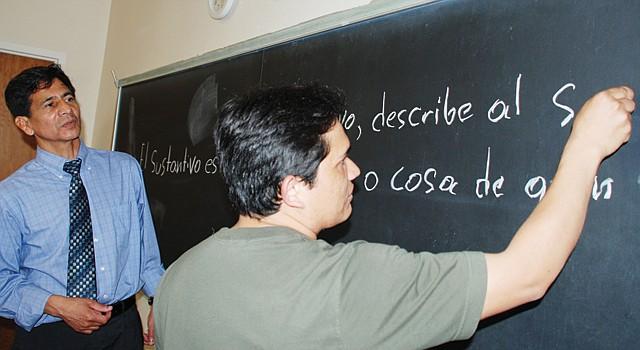 DICTADO. Joel López Nava (der.) escribe en la pizarra la definición del adjetivo. Mario Gamboa observa.