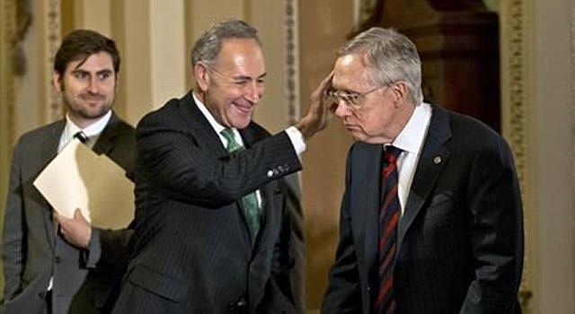 El senador líder de la mayoría demócrata en el Senador Harry Reid, de Nevada, derecha, junto al senador demócrata Charles Schumer, de Nueva York, izquierda, uno de los autores del proyecto de reforma migratoria arriban a una rueda de prensa en el Capitolio en Washington, el martes 25 de junio de 2013.