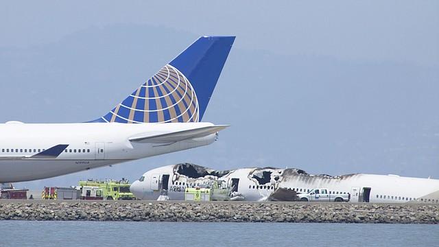 El avión del vuelo 214 de Asiana Airlines (der.) siniestrado en la pista del Aeropuerto Internacional de San Francisco, California, el sábado 6 de julio.