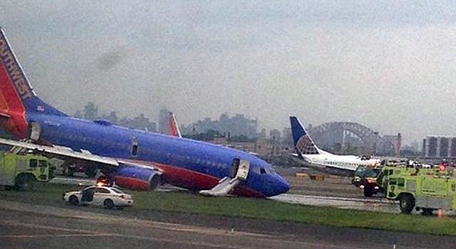 Un avión de Southwest Airlines, cuyo tren de aterrizaje delantero se dobló al aterrizar, es rodeado de vehículos de emergencia en el Aeropuerto LaGuardia en Nueva York el lunes 22 de julio de 2013.