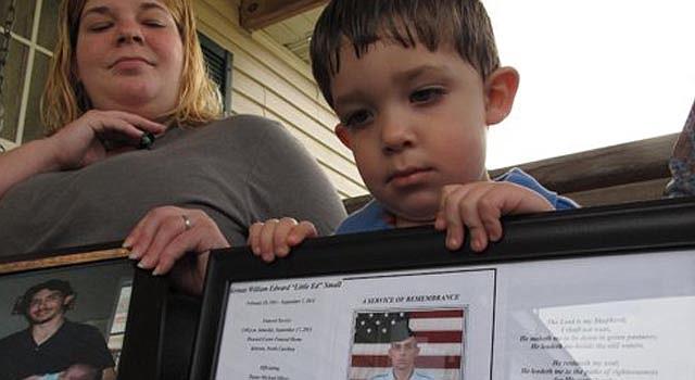 En esta foto del 18 de marzo del 2013, Shane Mercer muestra una foto de su padre, Will Small, mientras mira su madre Alecia Mercer en su hogar en Kinston, Carolina del Norte.