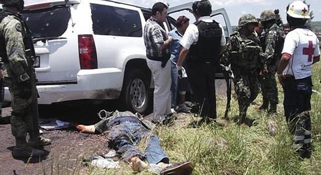 Elementos del Ejército, la Armada y la Policía Federal permanecen junto al vehículo de un vicealmirante de la Armada y un hombre muerto no identificado después de que fueron emboscados cerca del poblado de Churintzio, en el estado mexicano de Michoacán, el domingo 28 de julio de 2013.