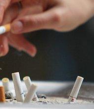 Una persona bota ceniza junto a colillas de cigarrillo. EFE/archivo.