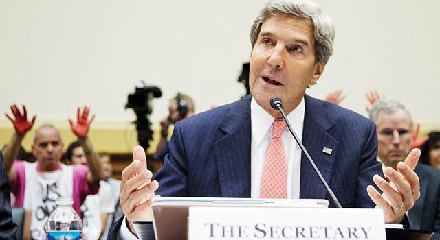 PROTESTA. Manifestantes muestran las manos pintadas de rojo mientras el secretario de Estado, John Kerry, testifica en el Capitolio el miércoles 4.