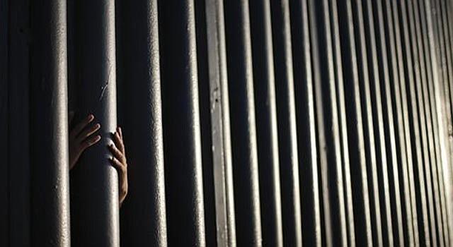En esta foto de archivo del 13 de jujnio de 2013, Daniel Zambrano, de Tijuana, México, aferra uno de los barrotes del muro fronterizo entre Estados Unidos y México, donde la frontera culmina en el Océano Pacífico en San Diego.