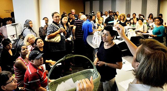 VIRGINIA. Jody Steiner Kelly, del Arlington Free Clinic realiza un sorteo, el 13 de agosto, entre los 130 asistentes que esperaban obtener una de las 28 citas que se dan al día. La clínica comunitaria es uno de los 1.200 centros del país que asisten a quienes no tienen seguro médico.