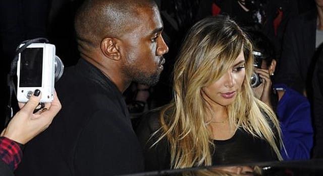 Kanye West, izquierda, y Kim Kardashian al salir del desfile de la colección primavera-verano de Givenchy en París en una fotografía del 29 de septiembre de 2013. Tras tener a su bebé Kim y Kanye están comprometidos, confirmó la representante de Kardashian el martes 21 de octubre de 2013.