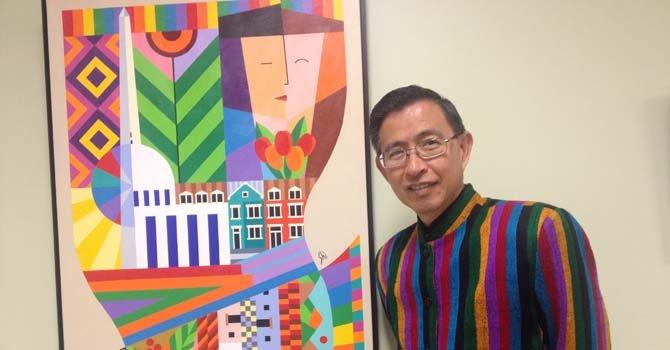 """El artista salvadoreño Nicolás F. Shi posa junto a una obra suya expuesta como parte de la muestra """"Herencia"""" en la Universidad Ana G. Méndez en Wheaton, Maryland. Shi vive en Washington, DC."""