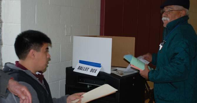 En algunos precintos como el 501, los votantes pudieron emitir su voto en papel, pasando por un escaner su boleta electoral. A la izq. el estudiante Sergio Martínez ayuda a un votante.