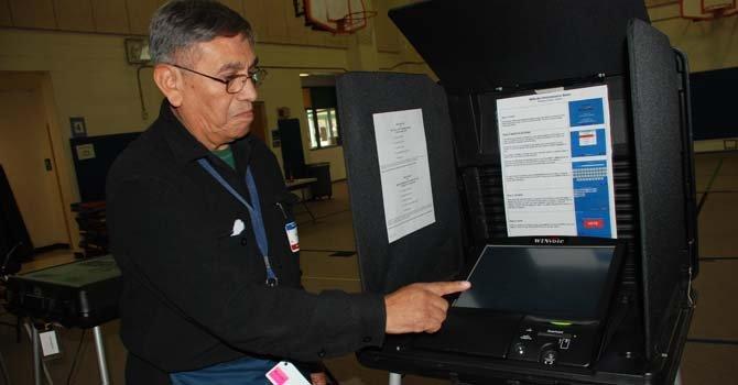 El oficial electoral Wiston Martínez, de Bolivia muestra la computadora para emitir el voto digital.