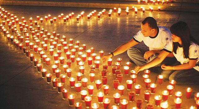 SOLIDARIDAD. Miembros de la Fundación Atlacatl Vivo Positivo encienden velas el 19 de mayo de 2013 en la capital de El Salvador.