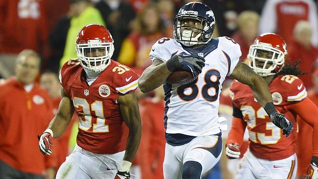 Demaryius Thomas (centro) de los Broncos de Denver corre con la pelota marcado por los jugadores de los  Kansas City Chiefs Marcus Cooper (izq.) y Kendrick Lewis en la segunda parte del partido del domingo 1 de diciembre en el Arrowhead Stadium de Kansas City, Missouri.